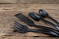 Шумовка черной пластичной кухни установленная, лопата сковороды на деревянном Стоковые Фотографии RF