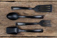 Шумовка черной пластичной кухни установленная, лопата сковороды на деревянном Стоковая Фотография