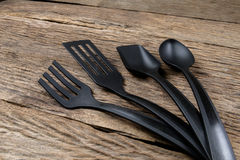Шумовка черной пластичной кухни установленная, лопата сковороды на деревянном Стоковые Изображения