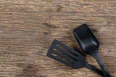 Шумовка черной пластичной кухни установленная, лопата сковороды на деревянном Стоковые Фото