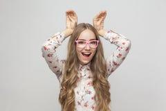 Шуточная женщина в розовых стеклах держа руки смотрит ` s как ухо кролика стоковое изображение rf