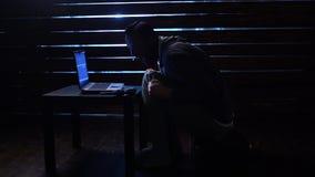 Шуточный смешной хакер совершает кибер атака с компьтер-книжкой и оружием в его руках сток-видео