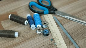 Шьющ поставляет ножницы, поток, катушкы, карандаш, правителя на деревянном столе акции видеоматериалы