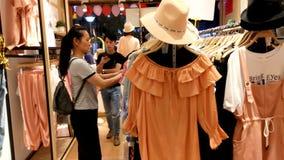 Шэньчжэнь, Китай: женщины покупают одежду и бюстгальтеры на магазине одежды акции видеоматериалы