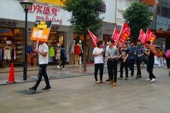 Шэньчжэнь, Китай: молодые люди для того чтобы поднять знамя рекламы интернета, бесплатного интернета публикуемости Стоковое Фото