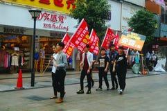 Шэньчжэнь, Китай: молодые люди для того чтобы поднять знамя рекламы интернета, бесплатного интернета публикуемости Стоковые Изображения RF