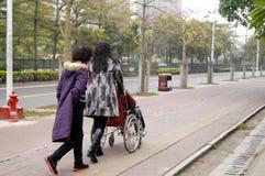 Шэньчжэнь, Китай: нажатие пожилых людей кресло-коляскы связанных Стоковые Фотографии RF