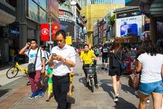 Шэньчжэнь, Китай - 16-ое июля 2018: Занятая улица пешехода людей Дуна стоковое фото