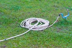 Шланг сада или белая резиновая трубка с faucet на поле травы Стоковые Изображения RF