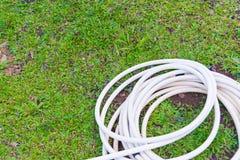Шланг сада или белая резиновая трубка с faucet на поле травы Стоковые Фото