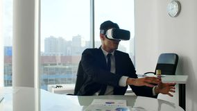 Шлемофоны виртуальной реальности молодого бизнесмена брюнет нося в белом будущем белом офисе сток-видео