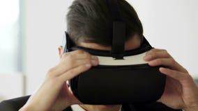 Шлемофоны виртуальной реальности молодого бизнесмена Portraite нося в белом будущем белом офисе Он щелкает его пальцы в акции видеоматериалы