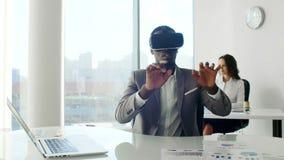 Шлемофоны виртуальной реальности молодого чернокожего человека нося в белом будущем белом офисе видеоматериал