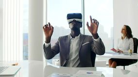 Шлемофоны виртуальной реальности молодого чернокожего человека нося в белом будущем белом офисе сток-видео
