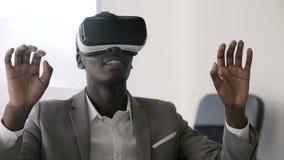 Шлемофоны виртуальной реальности молодого чернокожего человека нося в белом будущем белом офисе Он щелкает его пальцы в воздухе и акции видеоматериалы