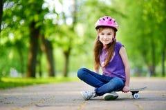 Шлем милой маленькой девушки preteen нося сидя на скейтборде Стоковое Изображение