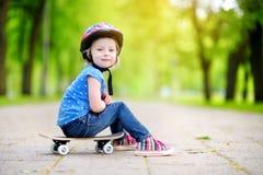 Шлем милой маленькой девушки preteen нося сидя на скейтборде Стоковая Фотография RF