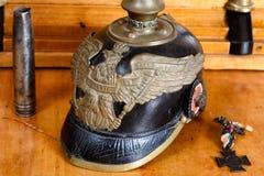 Шлем немецкой армии (Pickelhaube) от первой мировой войны на античном столе древесины вишни Стоковая Фотография