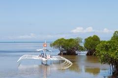 Шлюпка аутриггера поставленная на якорь в Shallows мангров Стоковое Фото
