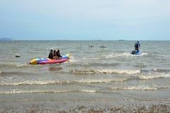 шлюпка банана лыжи двигателя волоча с путешественником от пляжа к морю Стоковые Изображения RF
