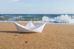 Шлюпка белой бумаги на пляже Стоковые Фотографии RF