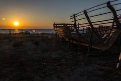 Шлюпка взморьем на заходе солнца Стоковые Фотографии RF