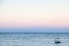 Шлюпка в море в голубом и розовом сумерк лета Стоковые Фото