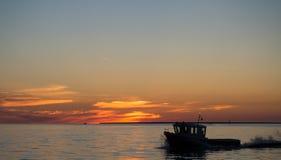 Шлюпка в море когда заход солнца Стоковое фото RF