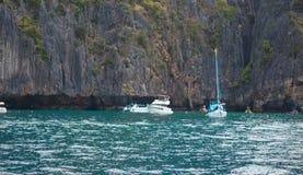 Шлюпка в море около скалистого берега Стоковая Фотография RF