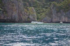 Шлюпка в море около скалистого берега Стоковое Изображение