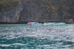 Шлюпка в море около скалистого берега Стоковые Изображения RF