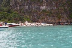 Шлюпка в море около скалистого берега Стоковая Фотография