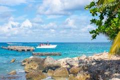Шлюпка в ясном океане на предпосылке пальм и красивых облаков Стоковые Фотографии RF