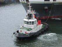 Шлюпка гужа вытягивая большой контейнеровоз в гавани Южной Африке Дурбана Стоковое Изображение