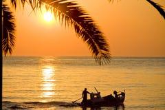 Шлюпка и пальма захода солнца Стоковое фото RF