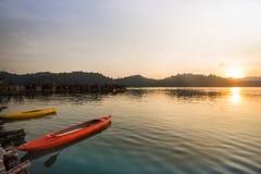 Шлюпка каяка на озере с красивой сценой захода солнца Стоковые Фото
