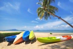 Шлюпка каяка с пальмами кокоса и тропической предпосылкой пляжа Стоковое Изображение RF