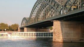 Шлюпка круиза на мосте Кёльна железнодорожном сток-видео