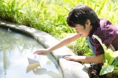Шлюпка мальчика плавая бумажная Стоковая Фотография RF