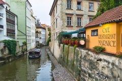 Шлюпка на канале в Праге на день около дома и кафе на портовом районе Стоковые Фотографии RF