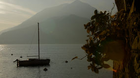 Шлюпка на озере Como на заходе солнца Позитивные стороны в озере Como на заходе солнца стоковые изображения