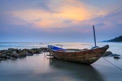 Шлюпка на пляже в заходе солнца Стоковое Фото