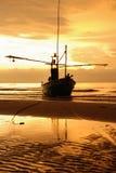 Шлюпка на пляже на времени восхода солнца Стоковое Фото