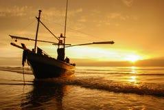 Шлюпка на пляже на времени восхода солнца Стоковые Фото