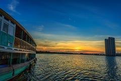 Шлюпка пассажира на береге реки с заходом солнца Стоковая Фотография RF