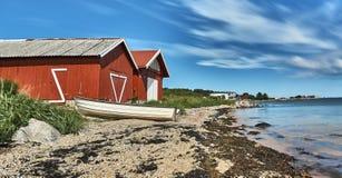 Шлюпка перед rorbu на пляже Стоковое Фото