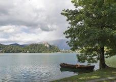 Шлюпка причаленная в тени дерева на озере кровоточила Стоковое Изображение