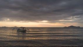 Шлюпка плавая на заход солнца Стоковое фото RF