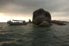 Шлюпка скалистого острова и рыболова Стоковое Изображение
