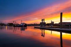 Шлюпка службы береговой охраны вытягивая в гавань и приходя домой на заход солнца Стоковые Изображения RF